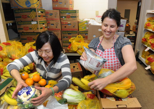 VANCOUVER, B.C.: JANUARY18, 2013 --  Program assistants Vuongmy (L) and Lorraine Holubowich prepare some of the thousands of pounds of food that they give out to families of children attending Strathcona Elementary School. This week, a donor has offered $30,000 to help renovate the food handling areas in the centre which can't deal with the amount of food necessary to feed the kids over the weekend. January 18, 2013 . (photo by Jenelle Schneider/PNG)(Vancouver Sun story by Gerry Bellett) [PNG Merlin Archive]